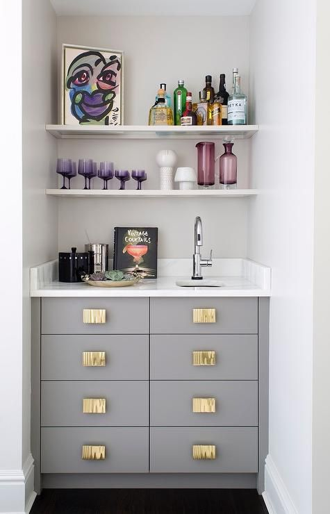 a small yet chic built-in bar with a sink, open shelves, drawers and a marble countertop plus colorful glass