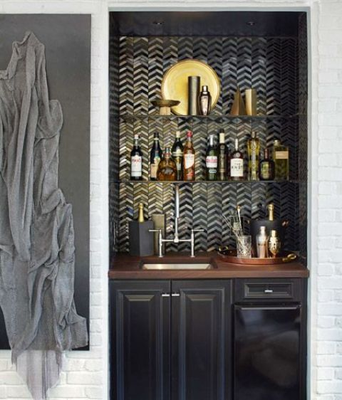 a small yet refined built-in bar with a tile backsplash, a black cabinet with a sink and touches of gold
