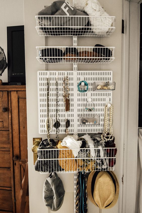 a smart organizer and storage unit attached to the closet door - wire baskets and a board for jewelry are a cool way to organize