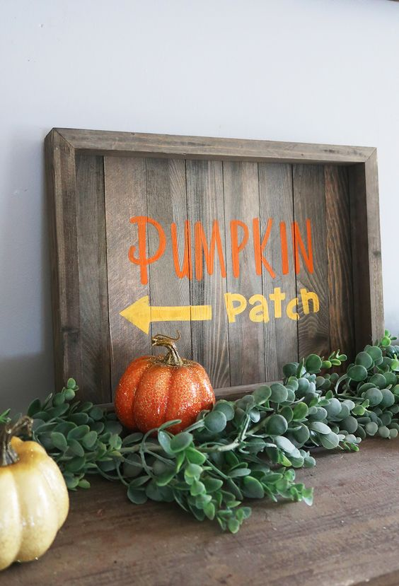 a stained fall sign with colorful letters, fresh greenery and colorful faux pumpkins