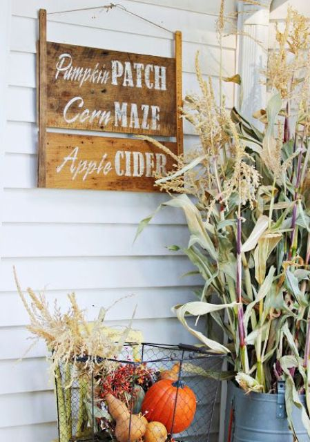 a stained wooden sign with white letters and a wire basket with fall veggies and greenery for a fall touch