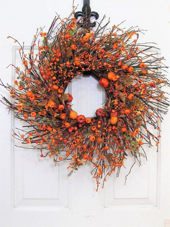 a statement fall twig wreath with orange faux pumpkins, berries, leaves and some greenery will accent your porch