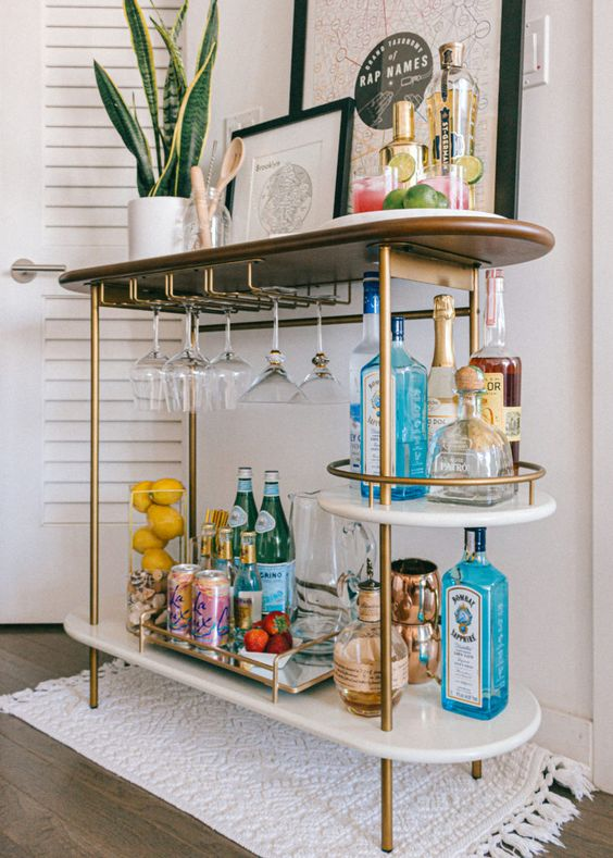 a stylish bar cart in brass, with open storage compartments, some artworks and a potted plant