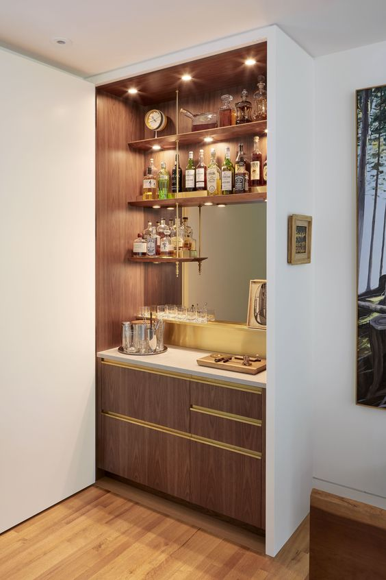a stylish built-in bar with open shelves, a mirror, sleek drawers and lights is a cool and chic idea