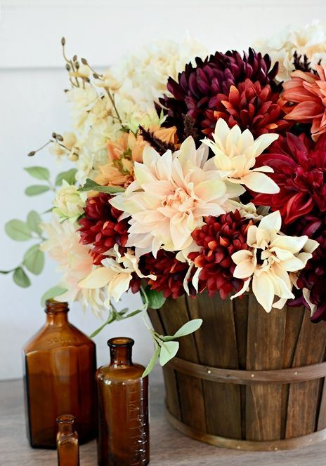 a stylish fall arrangement of blush, white and burgundy faux blooms in a basket is a cool rustic piece to rock