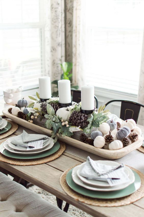a stylish fall centerpiece of a white bowl with pinecones and mini pumpkins and pillar candles in the center