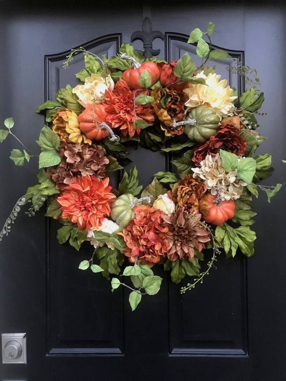 a stylish fall wreath of greenery, faux pumpkins and bright blooms is a cool decoration to rock