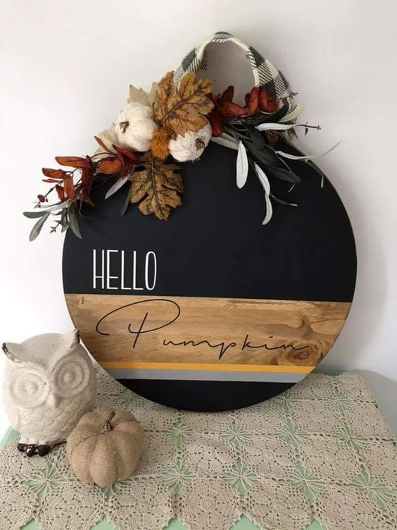 a stylish round fall sign done with staining and black paint, topped with leaves, yarn pumpkins and plaid ribbon
