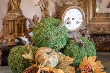 a stylish rustic fall arrangement of moss pumpkins, faux leaves, pumpkins of plastic, berries and pinecones for a woodland or rustic feel