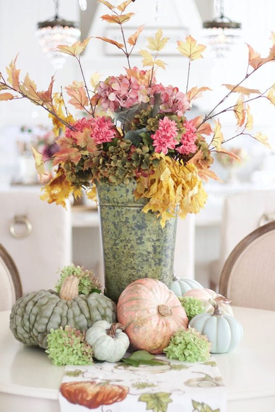 a stylish rustic fall decoration of a bucket with pink and green faux blooms, branches with leaves and heirloom pumpkins