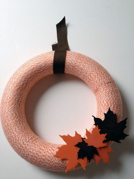 a stylish yarn fall wreath with orange yarn, colorful fabric leaves and a dark ribbon is a cool decoration