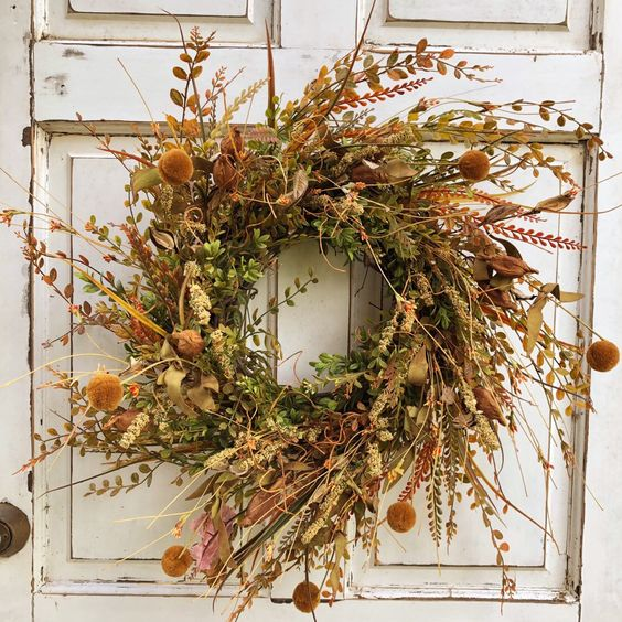 a super textural fall wreath with twigs, fall foliage, billy balls, grasses and some wildflowers is a cool fall decoration