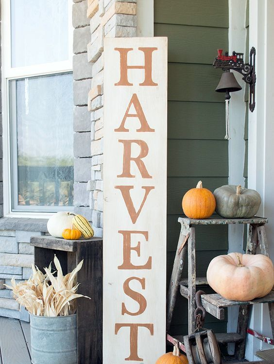 a tall Harvest sign, corn husks in a bucket and various colorful pumpkins around for a fall feel