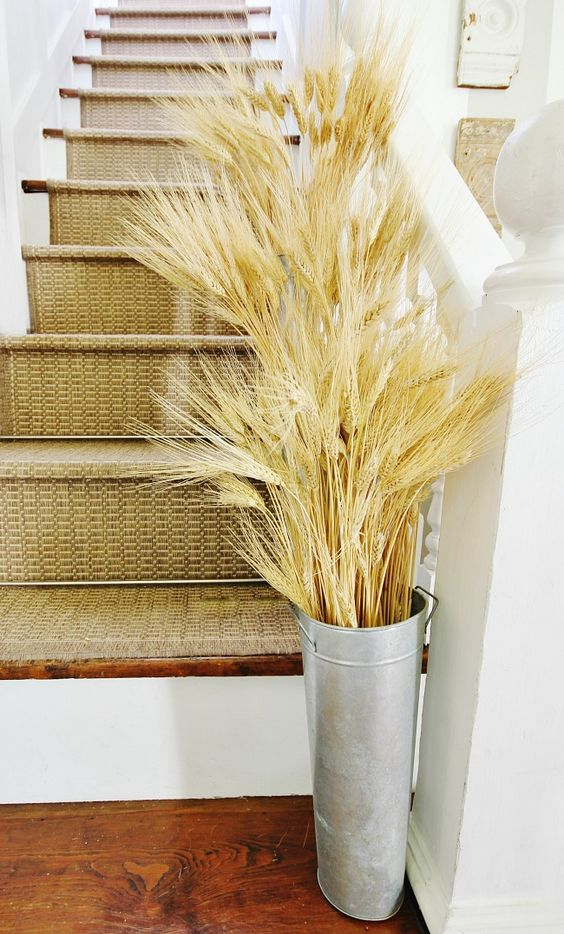 a tall and thin bucket with lots of wheat placed at the stairs to accent this zone and bring a fall feel to the space