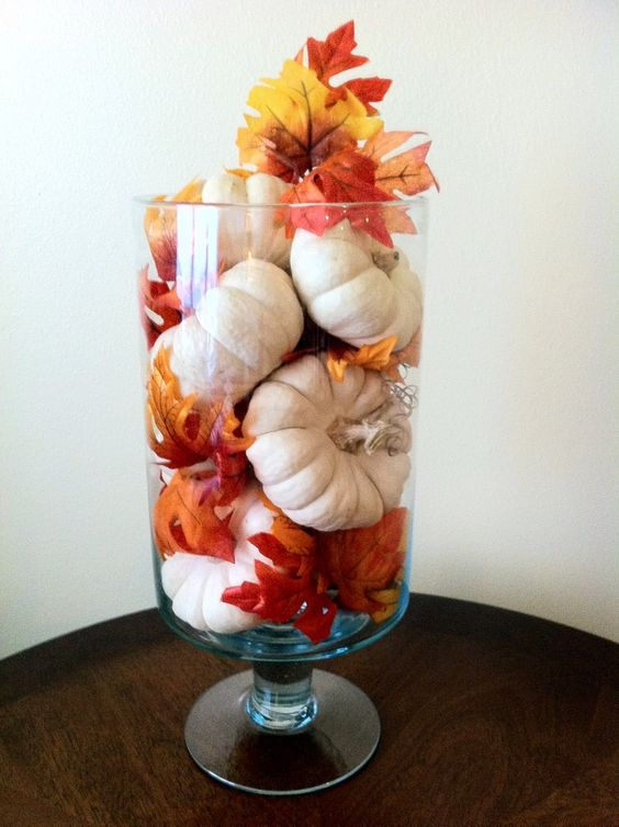 a tall glass vase with white pumpkins and bright fall leaves is a very easy arrangement for a bold look