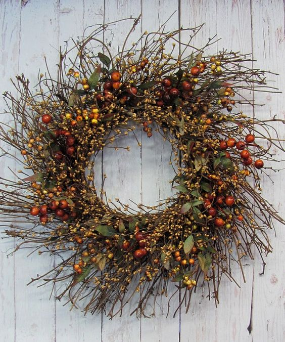 a textural twig fall wreath with foliage, berries and blooming branches is a cool fall decoration