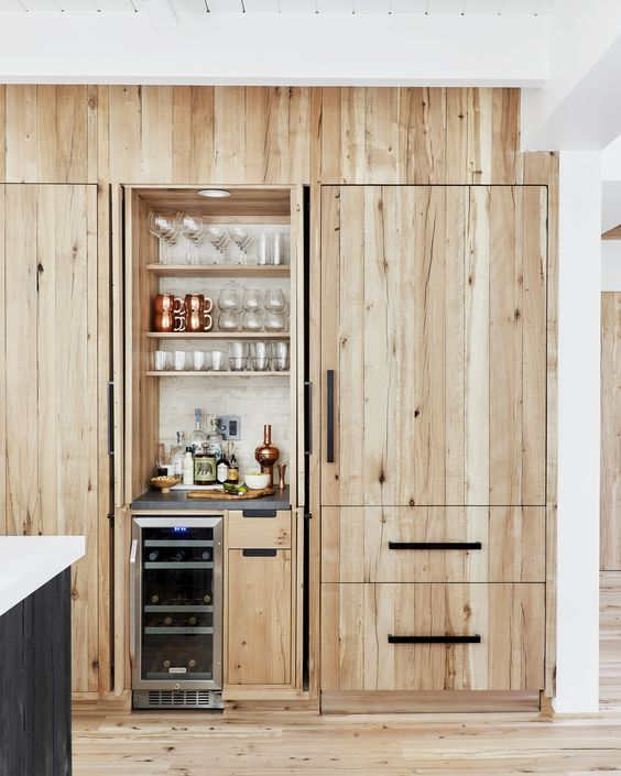 a tiny built-in bar with open shelves, a fridge and drawers with everything necessary looks natural in the kitchen