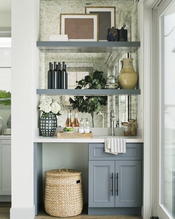 a tiny built-in home bar with a mirror backsplash, open shelves, a cabinet and a sink plus blooms and a basket