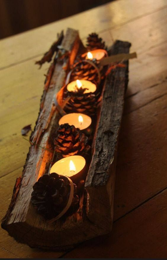 a tree stump with pinecones and tealights is a cool rough rustic centerpiece that will scream fall