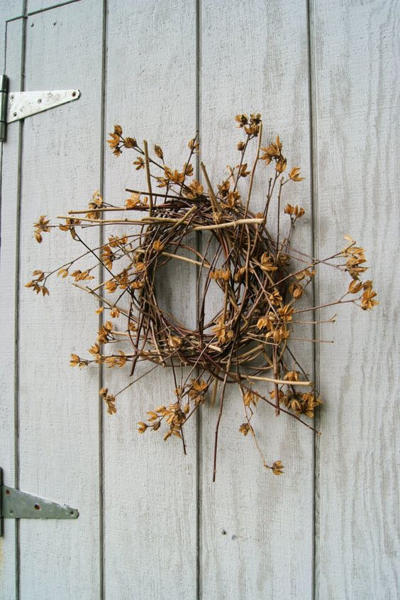 a twig and stick fall wreath with dried blooms and leaves is a simple and cool fall decoration with a decadent feel