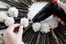 a twig and stick wreath with white pompoms is an easy and long-lasting decoration for the fall