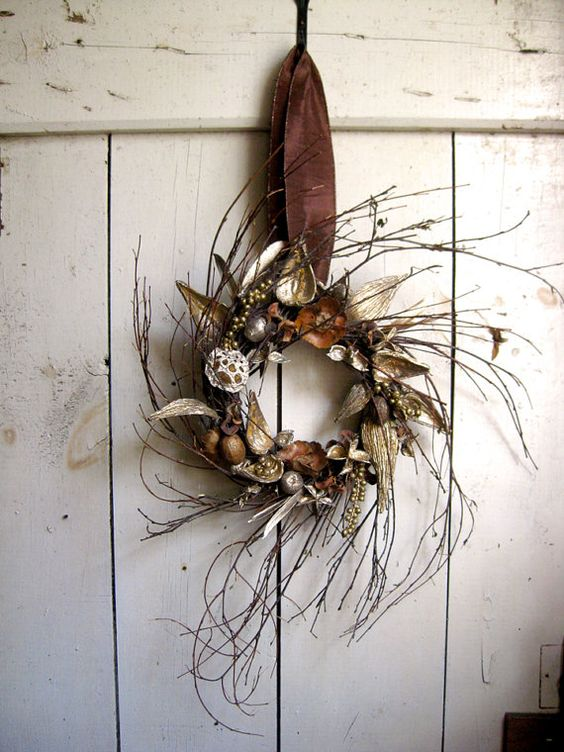 a twig fall wreath with acorns, dried leaves, nuts and gilded berries is a simple and natural idea