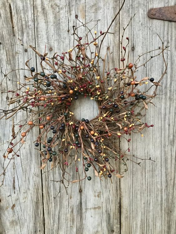 a twig fall wreath with dried leaves and berries looks catchy and will be a fit for fall or Halloween