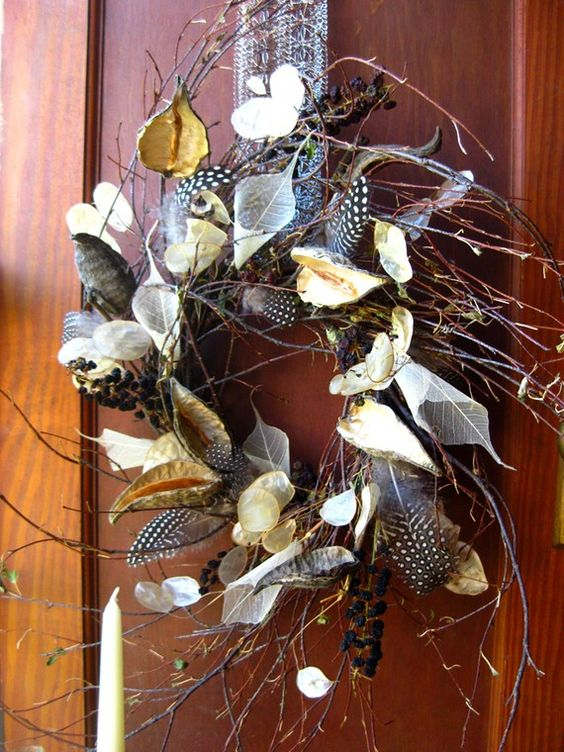 a twig fall wreath with dried leaves, blooms, feathers and berries looks boho-like and woodland-inspired