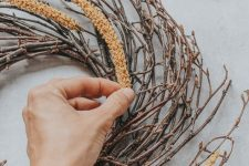 a twig wreath with dried elements attached to it is a lovely and non-typical decoration for the fall
