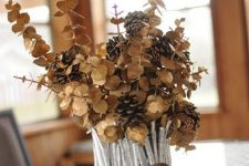 a vase covered with silver painted sticks and twigs, dried eucalyptus and pinecones is a chic fall centerpiece