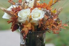 a vase with pebbles and rocks, dried fall leaves, white roses, wheat looks very chic and very natural