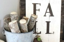 a very simple monochromatic fall sign and a bucket with cut branches and a plaid blanket for fall decor