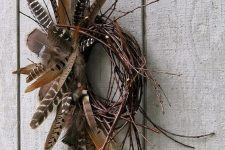 a vine and twig fall wreath with lots of various feathers is a gorgeous fall decoration to rock