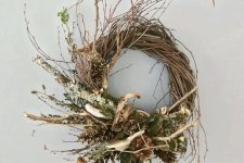 a vine and twig fall wreth with antlers, pinecones, dried leaves and moss is very woodland-like and cool