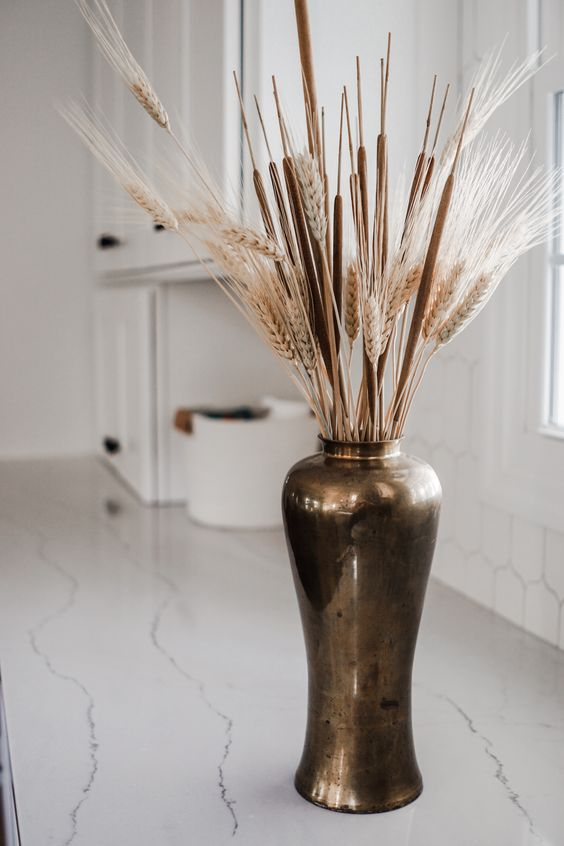 a vintage metal vase with cane and wheat is a cool fall decoration to go for