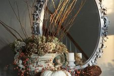 a vintage rustic decoration with lots of neutral pumpkins with berries, green hydrangeas and twigs and sticks