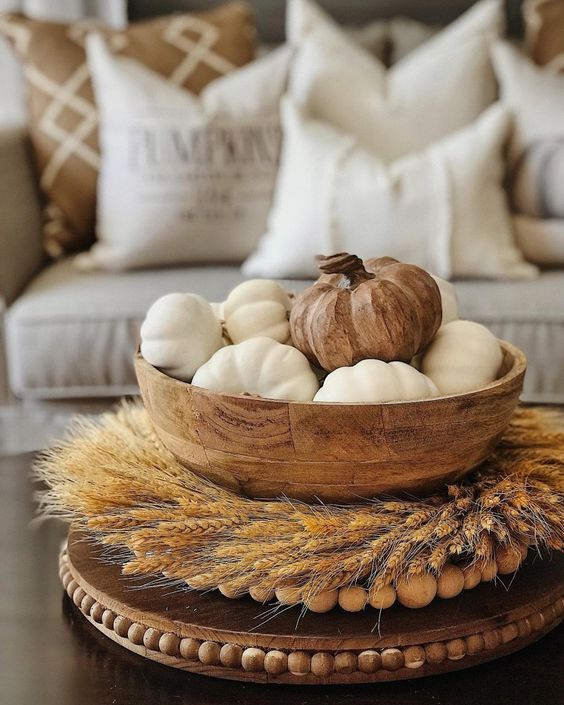 a wheat wreath surrounding a wooden bowl with white pumpkins and a wooden one for the fall