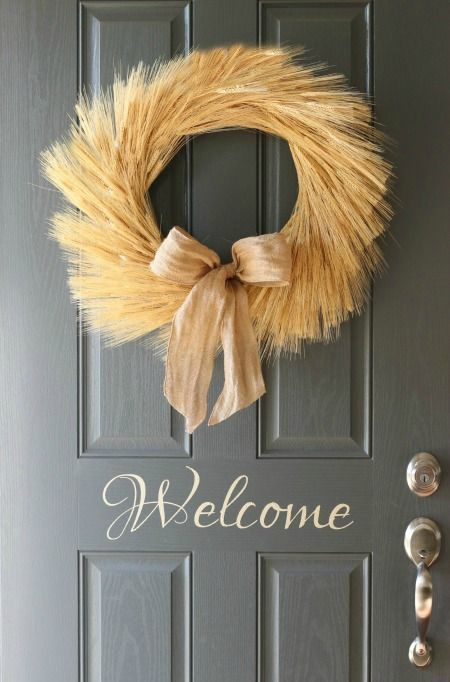 a wheath wreath with a burlap bow is a cool decoration for decorating your front door in fall style