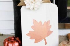 a white mason jar with leaf fall sign with a burlap ribbon and a faux white flower for the fall