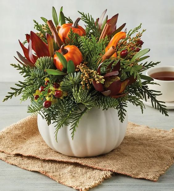 a white pumpkin with faux blooms, berries, greenery and faxu pumpkins and gourds for the fall