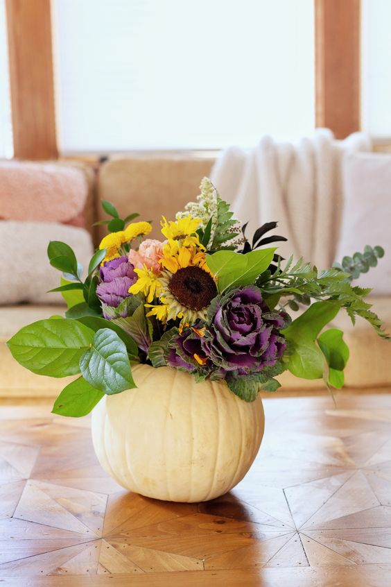 a white pumpkin with foliage, faux yellow and purple blooms and some dried touches is a chic fall centerpiece