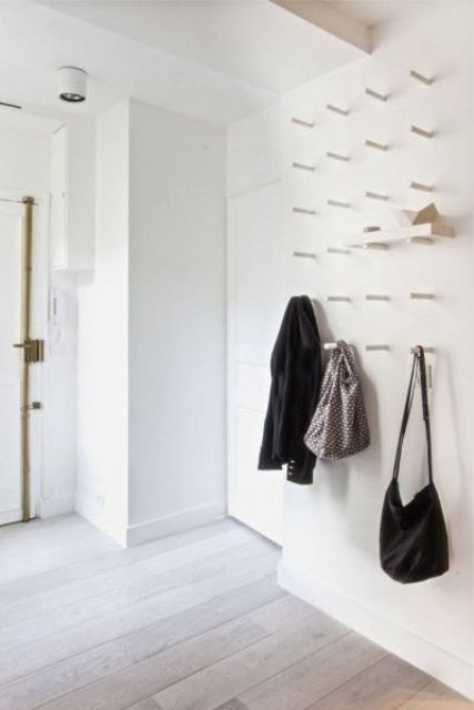 a white wall with lot sof hooks to hang clothes and bags or even place shelves and store shoes on them