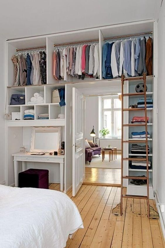 a whole open closet with lots of shelves is integrated over the door and on both sides to save as much space as possible