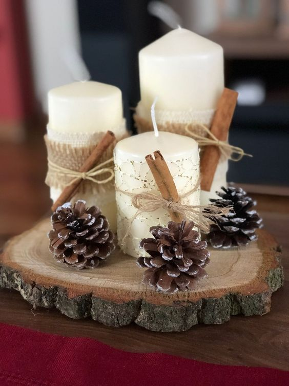 a wood slice with pinecones, pillar candles, cinnamon and burlap are a cool centerpiece for fall or winter