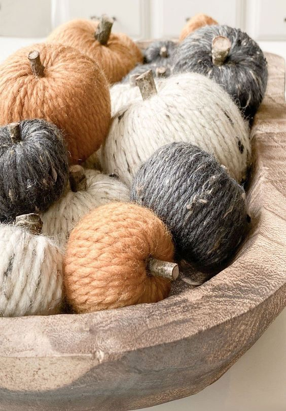 a wooden bowl with twine covered pumpkins and wooden stems is a simple rustic decoration for the fall