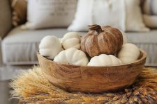 a wooden bowl with white faux pumpkins and a wooden one on top, a wheat wreath and wooden beads for a farmhouse space