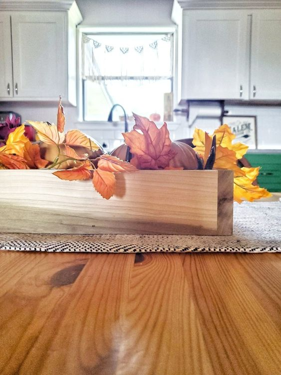 a wooden box centerpiece with faux pumpkins and fall leaves is a perfect match for a rustic table setting