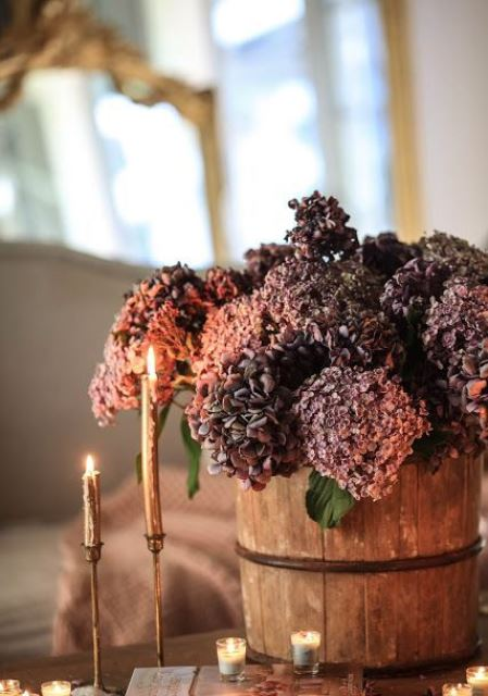 a wooden bucket with purple and rust-colored faux blooms plus elegant gold candles are a stylish combo for the fall