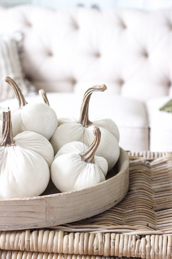 a wooden tray with white fabric pumpkins with natural stems is a simple and natural looking fall decoration or centerpiece