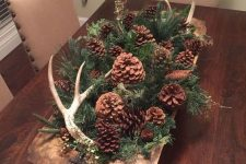 a woodland fall centerpiece of a dough bowl with evergreens, pinecones of various kinds and antlers for autumn